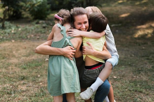 Mittlerer schuss lehrer und kinder umarmen sich
