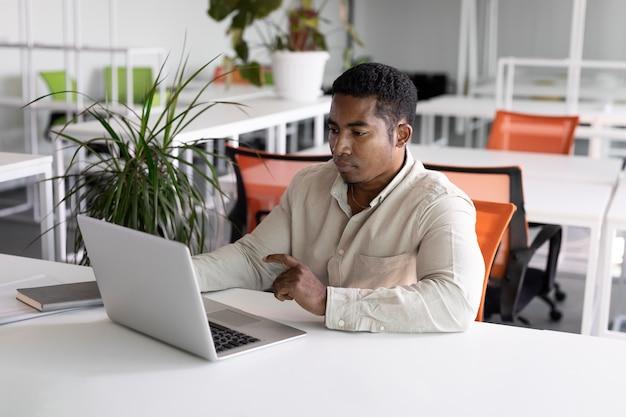 Mittlerer schuss mann bei job mit laptop