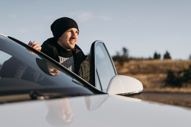 Mittlerer schuss mann, der aus dem auto steigt