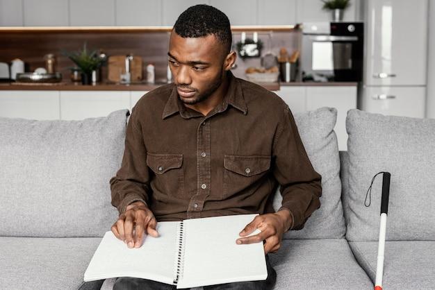 Mittlerer schuss mann, der braille-notizbuch hält