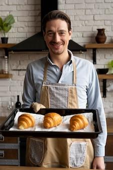Mittlerer schuss mann, der croissants tablett hält