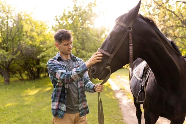 Mittlerer schuss mann, der draußen pferd streichelt