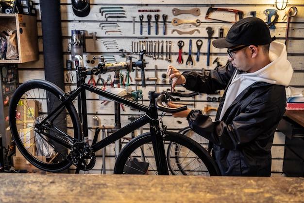 Mittlerer schuss mann, der fahrrad repariert