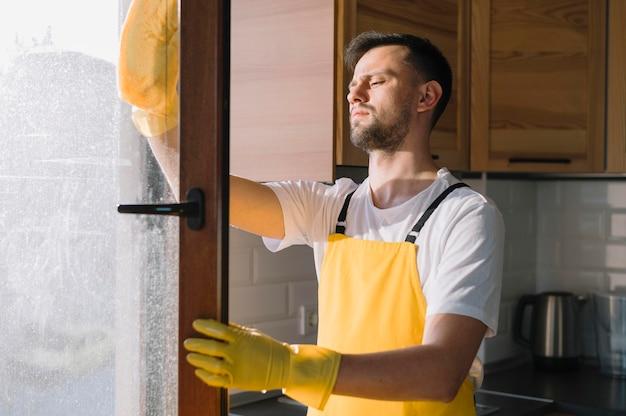 Mittlerer schuss mann, der fenster reinigt