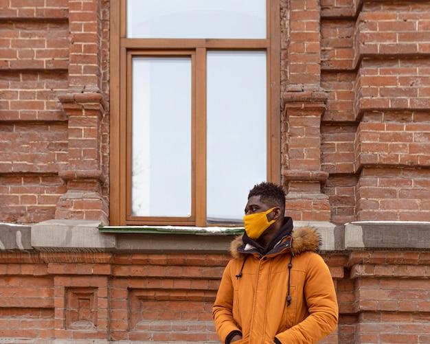 Mittlerer schuss mann, der gelbe maske trägt