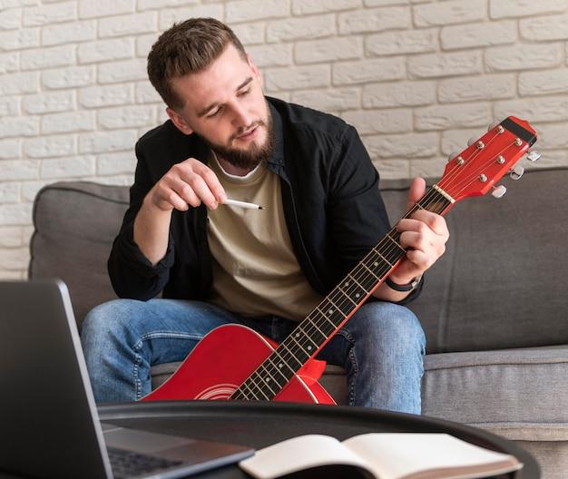 Mittlerer schuss mann, der gitarre hält