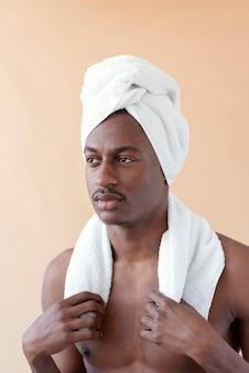Mittlerer schuss mann, der handtuch trägt