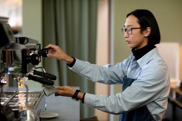 Mittlerer schuss mann, der kaffeemaschine putzt