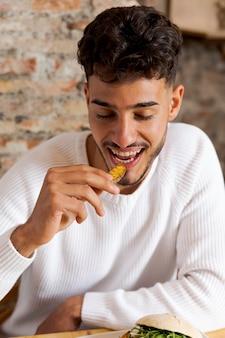 Mittlerer schuss mann, der kartoffel isst
