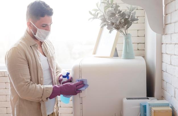 Mittlerer schuss mann, der kühlschrank desinfiziert