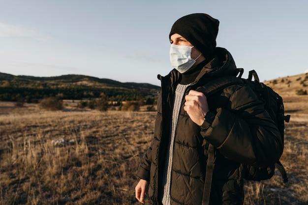 Mittlerer schuss mann, der maske trägt