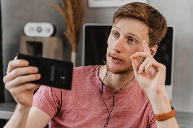Mittlerer schuss mann, der mit telefon strömt
