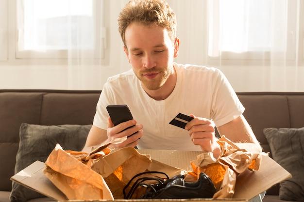 Mittlerer schuss mann, der online einkauft