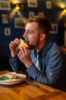 Mittlerer schuss mann, der sandwich isst