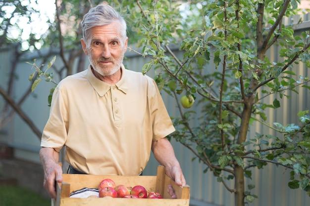 Mittlerer schuss mann, der schachtel äpfel hält