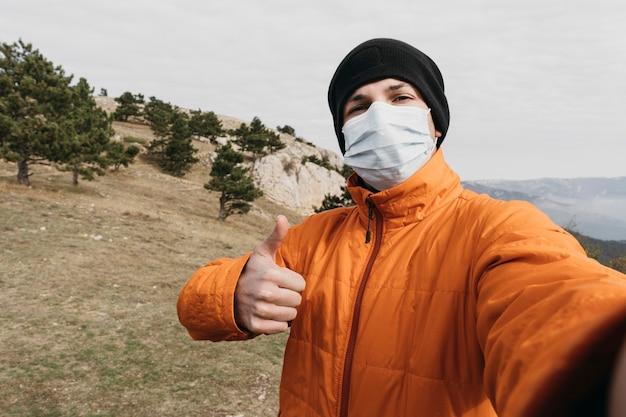 Mittlerer schuss mann, der selfie mit maske nimmt