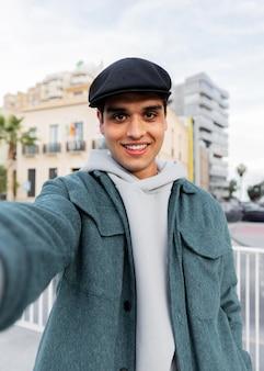 Mittlerer schuss mann, der selfie nimmt