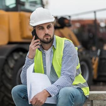 Mittlerer schuss mann, der über telefon spricht