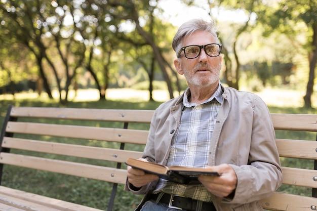 Mittlerer schuss mann mit buch im park