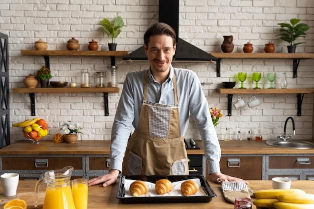 Mittlerer schuss mann mit croissants auf tablett