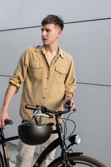 Mittlerer schuss mann mit fahrrad und helm