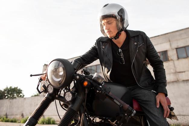Mittlerer schuss mann mit helm auf motorrad