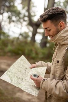 Mittlerer schuss mann mit karte und kompass