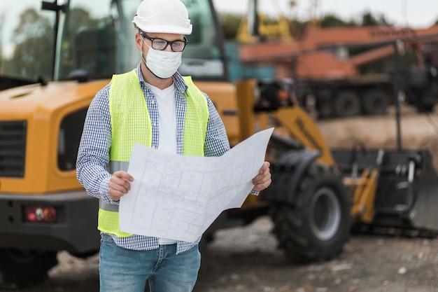 Mittlerer schuss mann mit maske und projekt
