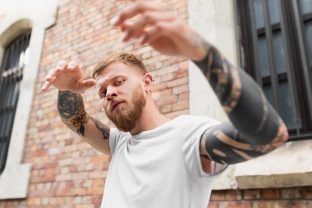 Mittlerer schuss mann mit tattoos posiert