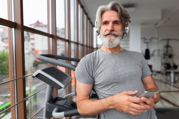 Mittlerer schuss mann mit telefon im fitnessstudio