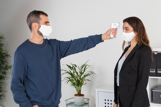 Mittlerer schuss mann mit temperaturvorrichtung