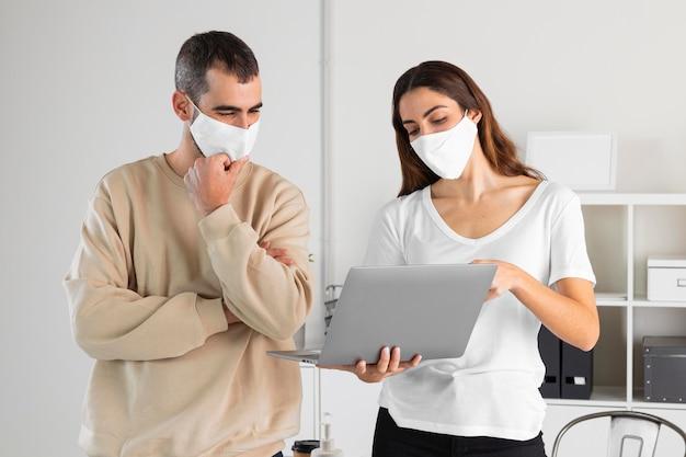 Mittlerer schuss mann und frau, die laptop betrachten