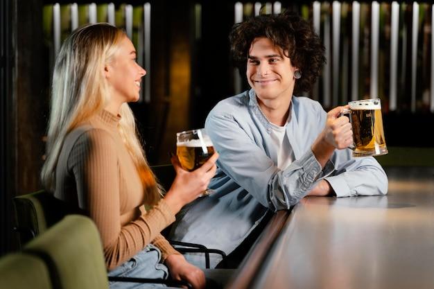 Mittlerer schuss mann und frau mit bierkrügen