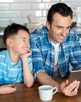 Mittlerer schuss mann und kind mit tablette