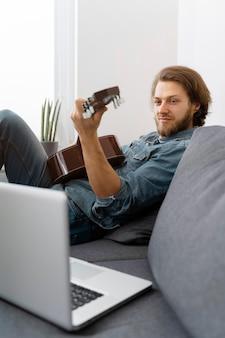 Mittlerer schuss mann zu hause mit gitarre