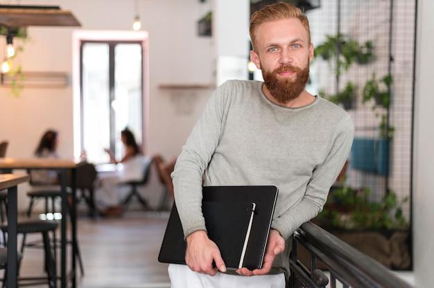 Mittlerer schuss moderner mann, der seinen laptop und sein notizbuch hält