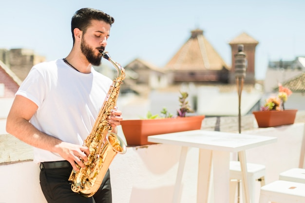 Mittlerer schuss seitlich mann, der das saxophon spielt