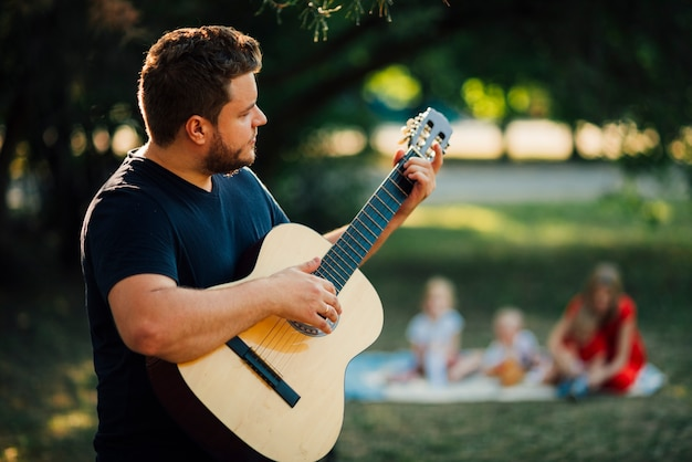 Mittlerer schuss seitlich vater, der gitarre spielt
