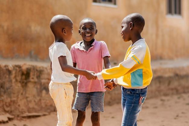 Mittlerer schuss smiley afrikanische jungen, die zusammen spielen