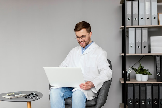 Mittlerer schuss smiley-arzt, der mit laptop arbeitet