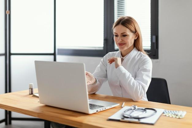 Mittlerer schuss smiley-arzt mit laptop