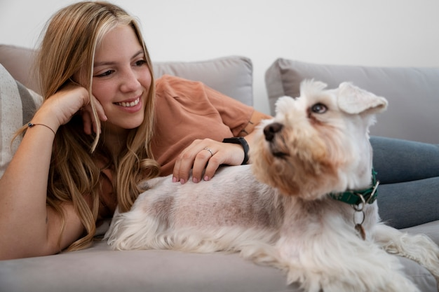 Mittlerer schuss smiley-frau, die hund streichelt