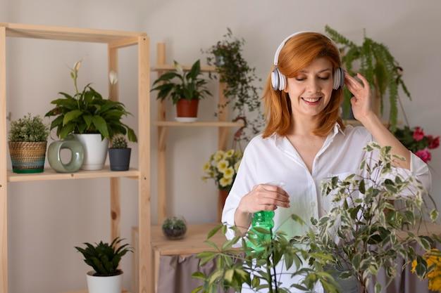 Mittlerer schuss smiley-frau, die pflanze gießt