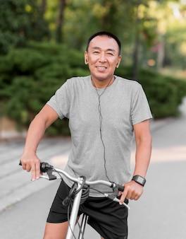 Mittlerer schuss smiley-mann auf fahrrad