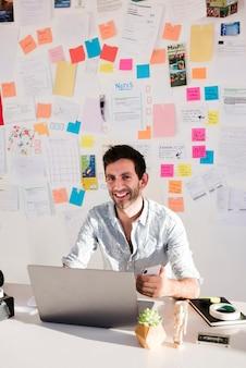 Mittlerer schuss smiley-mann, der am laptop arbeitet