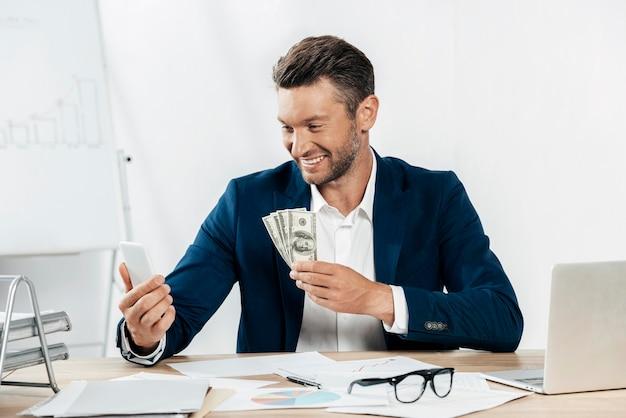 Mittlerer schuss smiley-mann, der banknoten hält