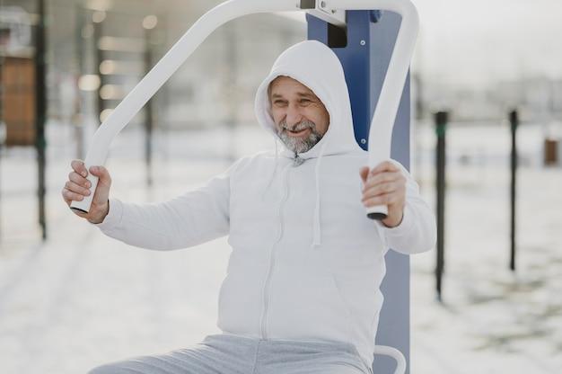 Mittlerer schuss smiley-mann, der draußen trainiert