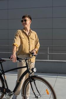 Mittlerer schuss smiley-mann, der fahrrad hält