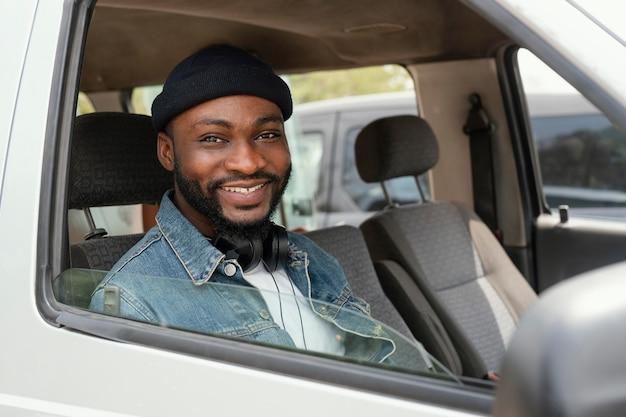 Mittlerer schuss smiley-mann, der im auto sitzt
