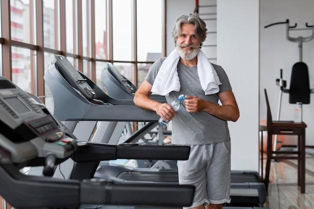 Mittlerer schuss smiley-mann, der im fitnessstudio aufwirft